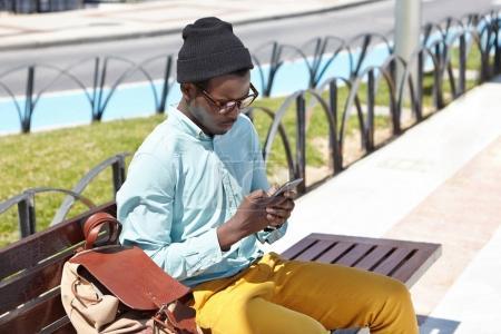 dark-skinned hipster using free city wi-fi