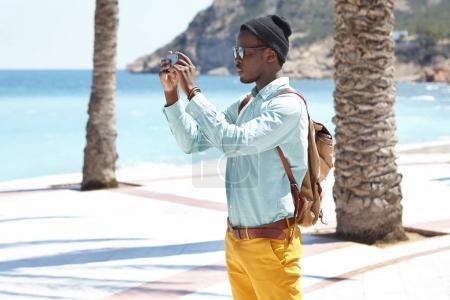 black traveler on vacations holding smartphone