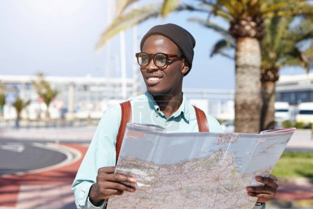 dark-skinned tourist studying city guide