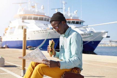 Afro American traveler studying city guide