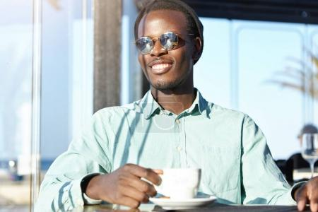Afro American student drinking fresh cappuccino