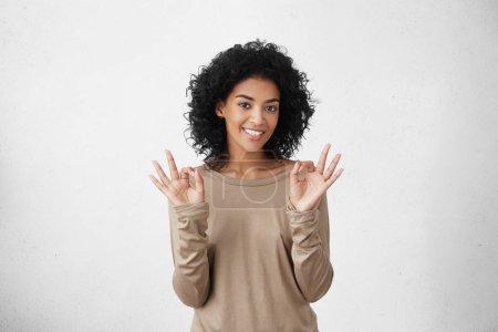 dark-skinned student girl showing OK