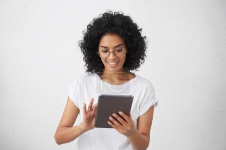 dark-skinned smiling female using tablet