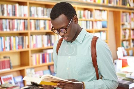 African American student looking through book