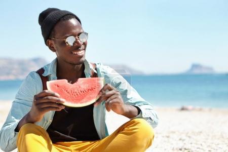 African man eating ripe watermelon