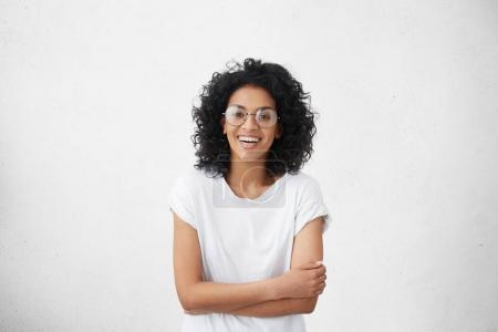 Photo for Indoor portrait of beautiful young dark-skinned woman wearing big round eyeglasses and casual white t-shirt smiling joyfully, keeping arms crossed, laughing out loud while watching comedy on TV - Royalty Free Image