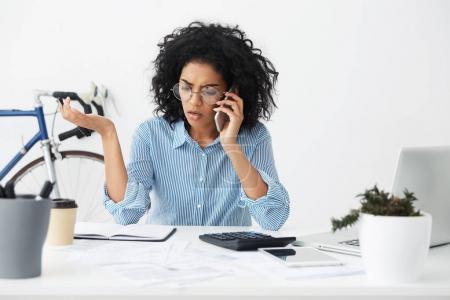 businesswoman having stressful phone conversation