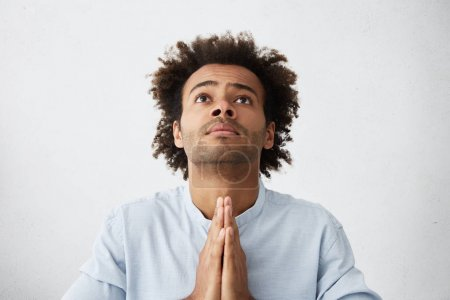 man pressing palms together in prayer