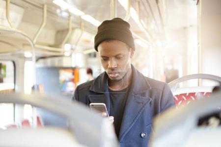 dark-skinned man in tram looking at phone