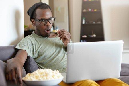 dark-skinned man watching films