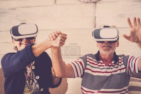 elderly couple with virtual reality headset goggle eyeglass playing together at home with fun. hand on hand with smiles