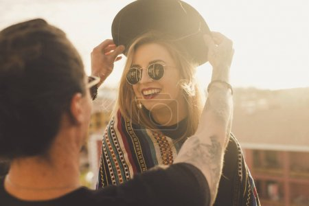 outdoor activity for couple of man and blonde young beautiful woman having fun together. he puts a hat on her head and she smile. sunlight and rooftop scene