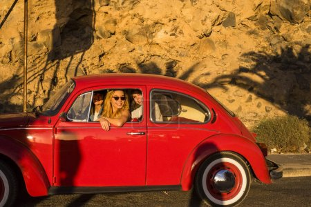 team of friends travel inside an old red car. Enjoy together the lifestyle and the vintage vehicle. Beautiful funny sunny day in Tenerife.
