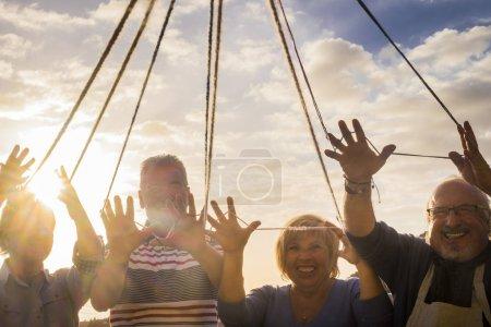 Photo pour 4 messieurs aux cheveux blancs jouent avec des fils de laine enveloppés dans leurs doigts. Rire et s'amuser sur la terrasse. Tous unis les mains en l'air. Comme un fond le ciel avec des nuages et le soleil . - image libre de droit