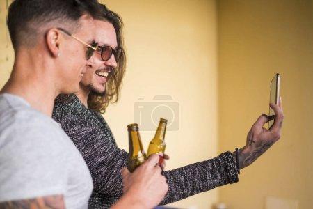 Foto de Hermosa pareja de hombres caucásicos mirar el teléfono tomando fotos. cerveza y diversión sonriendo al aire libre se centran en el segundo hombre. toatto y concepto de moda - Imagen libre de derechos