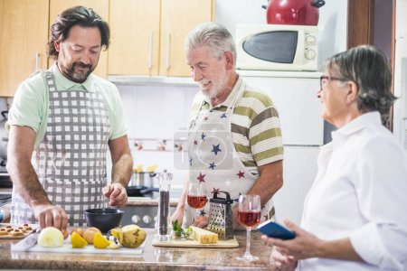 home work scene for a family with father mother and son. middle age and seniors adults with white hair stay together cooking the dinner and drinking wine.