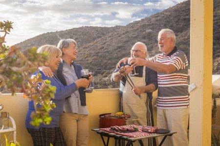 Foto de Grupo de personas adultas mayores en actividades de ocio haciendo parrilla barbacoa en la terraza de la azotea en casa con vista a la montaña. comida y vino para dos hombres y dos mujeres que se divierten juntos bajo la luz del sol en vacaciones - Imagen libre de derechos