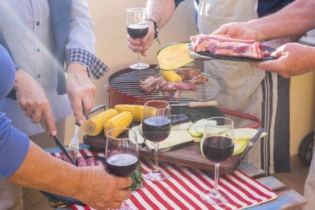 Foto de De cerca con un montón de manos de preparar comida con barbacoa al aire libre. alimentos frescos como comida y vegetales y mais palomitas de maíz cocinan al fuego. Grupo de personas en una actividad agradable para ancianos - Imagen libre de derechos