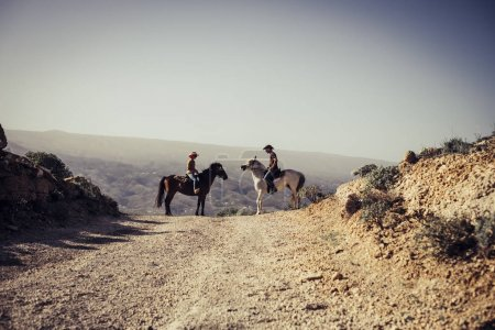 couples of horses and riders man and woman in love in the nature countryside. freedom and alternative lifestyle concept for modern cowboy and cowgirl in leisure activity at the mountains