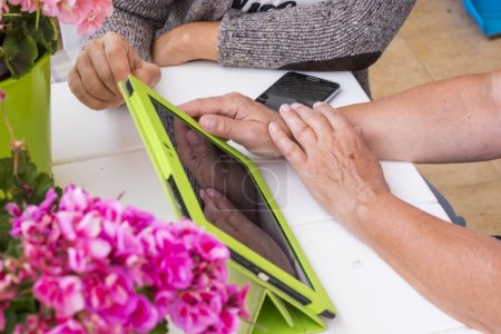 close up of different ages hands from senior to middle age using a tablet to communicate with modern wifi with friends that live far away. caucasian friends women at work outdoor