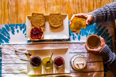 Photo pour Femme prenant le petit déjeuner avec du pain grillé et de la marmelade à la maison - image libre de droit