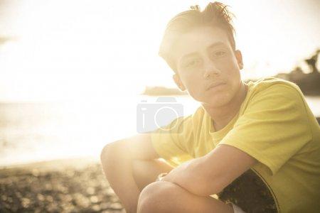 Photo pour Beau portrait jeune beau garçon adolescent regardant la caméra assis à la plage avec coucher de soleil soleil dans la lumière du dos - image libre de droit