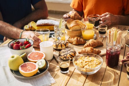 Photo for Close up of group of unrecognizable people eating breakfast all together on a wooden table - Royalty Free Image