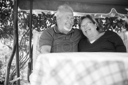 Photo pour Beau couple de belle caucasienne senior 70 ans assis en plein air à la maison en s'amusant avec des sourires et rire - image libre de droit