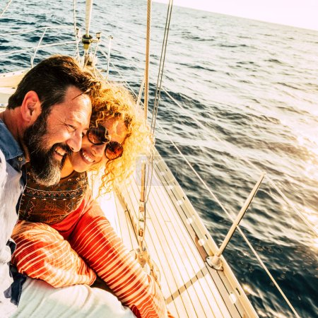 Happy and cheerful caucasian couple enjoy the sail boat trip together