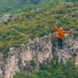 A man is walking along a stretched sling. Highline...