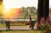 Lonely young woman sitting on a bench in the park
