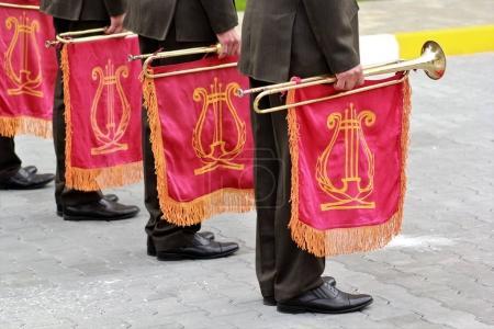 Photo pour Défilé de l'orchestre militaire tenant trompette instrument de musique avec le drapeau rouge et or lyre là-dessus - image libre de droit