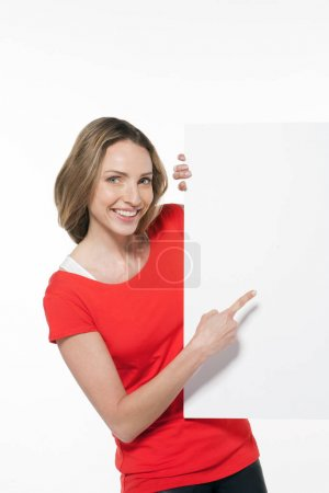 Happy woman showing blank space on white board