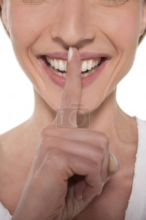 Happy woman with finger on mouth