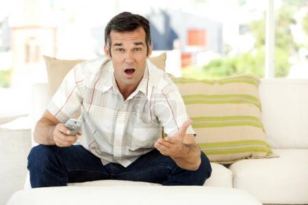 Photo pour Seul moyen homme caucasien âgé à domicile regardait la télévision - image libre de droit