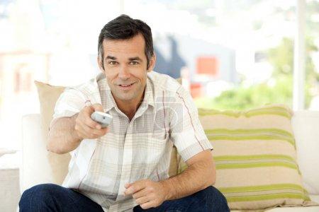 Photo pour Célibataire d'âge moyen homme caucasien à la maison regarder la télévision - image libre de droit