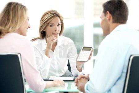Photo pour Femelle conseiller financier montrant les chiffres sur la calculatrice pour jeune couple à la Banque - image libre de droit