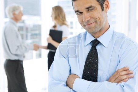 Photo pour Portrait d'un homme d'affaires mature heureux au premier plan avec des partenaires d'affaires secouant les mains dans le fond - image libre de droit
