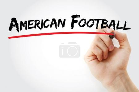 Hand writing American football with marker