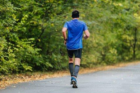 Photo pour Yalta - 5 octobre 2016 : Athlète masculin d'âge moyen en course au marathon du Parc d'automne. jambes chaussettes de compression - image libre de droit