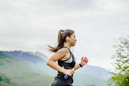 Photo pour Rosa Khutor, Russie - 7 mai 2017 : jeune fille coureuse avec un gel nutritif énergétique à la main en course marathon de montagne de printemps - image libre de droit
