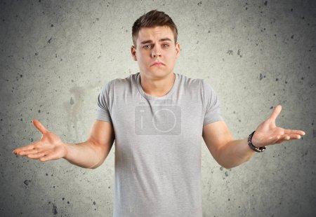 Young man shrugging shoulders
