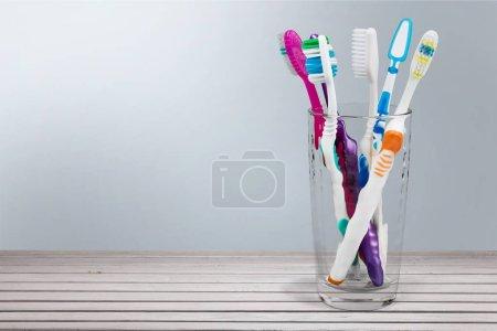 Photo pour Nouvelles brosses à dents colorées dans un verre sur fond - image libre de droit
