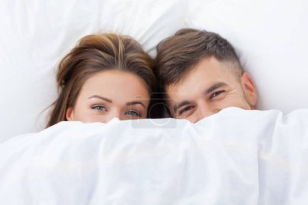 funny couple in love lying in the bed