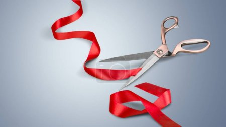 Scissors and red ribbon on a white