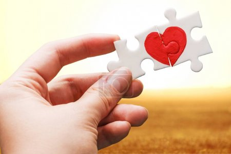 Photo for Hand holding puzzle pieces with painted red heart on background - Royalty Free Image