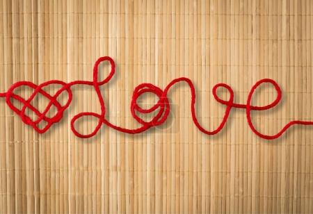 text love with red heart from rope on brown background