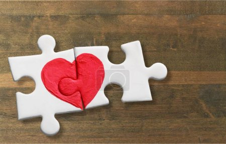 puzzle pieces with painted red heart on wooden background