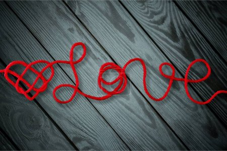 text love with red heart on wooden background