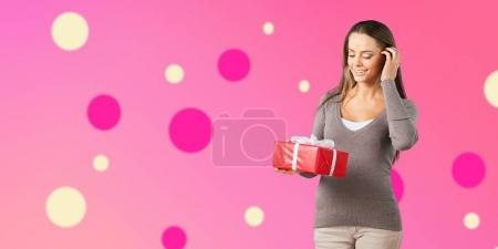 cute young woman holding big red gift in hands